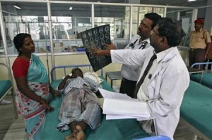 Doctors examine a MRI scan of a patient lying on a bed inside a ward at RGGGH in Chennai